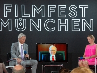Strategic investors. Dr. Stephan Goetz, Warren Buffett (on video link) and Baronin Ariane de Rothschild at the Munich Film Festival,2012 (Source: Wikimedia Commons)