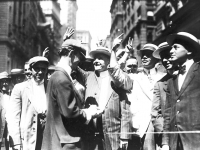 Stock trading on the New York Curb Association market, with brokers and clients signaling from street to offices, 1916 (Source: Wikimedia Commons)